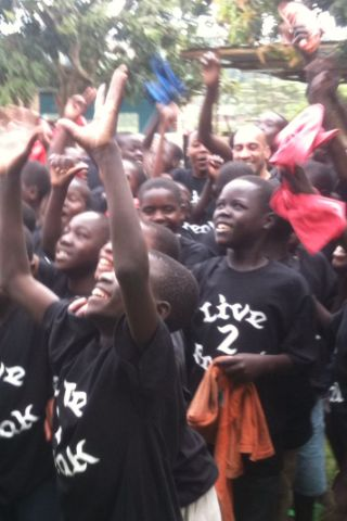Young Rwandan boys in Live 2 Break t-shirts cheering and smiling
